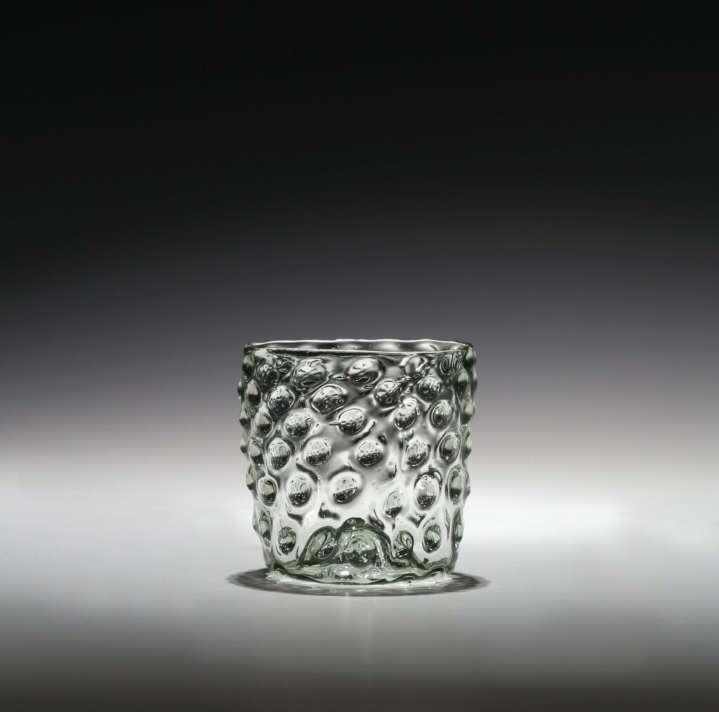A PALE-GREEN GLASS MOULDED BEAKER WITH RAISED BOSSES