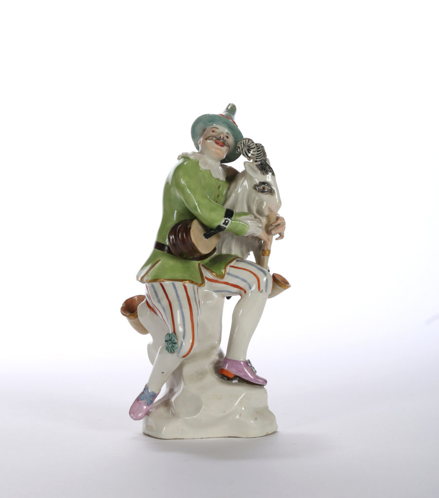 A HÖCHST FIGURE OF HARLEQUIN OR HANSWURST WITH BAGPIPE