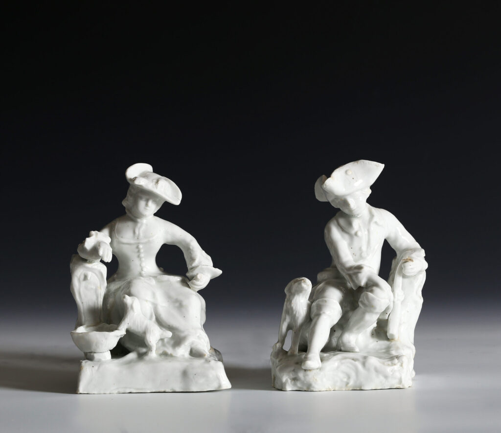 A PAIR OF BOW FIGURES OF A SEATED SPORTSMAN AND COMPANION